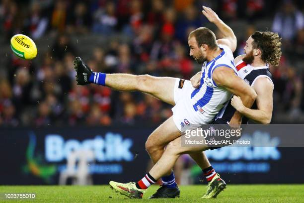 Ben Cunnington of the Kangaroos kicks the ball from Jack Steven of the Saints during the round 23 AFL match between the St Kilda Saints and the North...