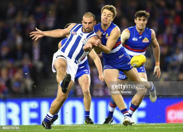 Ben Cunnington of the Kangaroos kicks whilst being tackled by Jackson Macrae of the Bulldogs during the round 14 AFL match between the Western...