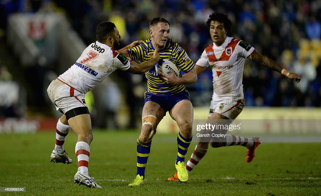 Ben Currie of Warrington Wolves is tackled by Benji Marshall of St George Illawarra Dragons during the World Club Series match between Warrington Wolves and St George Illawarra Dragons at The Halliwell Jones Stadium on February 20, 2015 in Warrington, England.