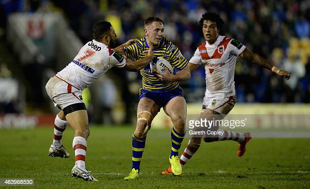 Ben Currie of Warrington Wolves is tackled by Benji Marshall of St George Illawarra Dragons during the World Club Series match between Warrington...
