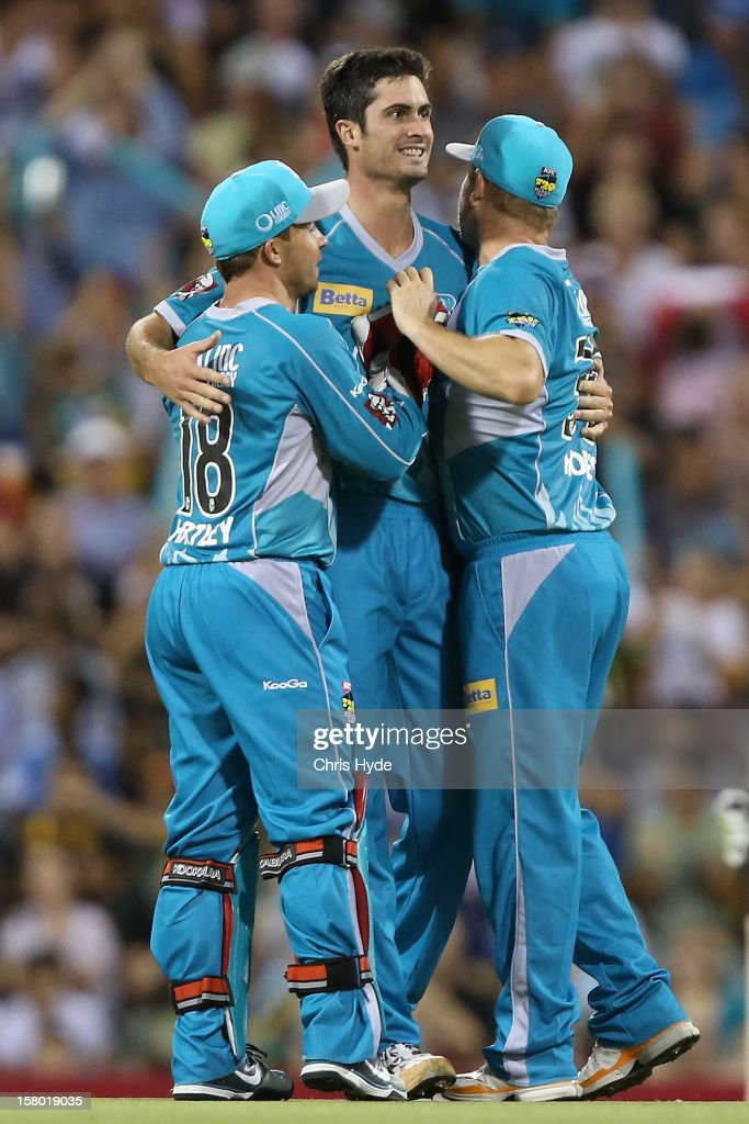 Ben Cutting of the Heat celebrates with team mates after dismissing Jon Wells of the Hurricanes during the Big Bash League match between the Brisbane Heat and the Hobart Hurricanes at The Gabba on December 9, 2012 in Brisbane, Australia.