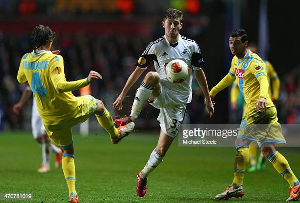 Ben Davies of Swansea City is challenged by Henrique of SSC Napoli during the UEFA Europa League Round of 32 First Leg match between Swansea City and...