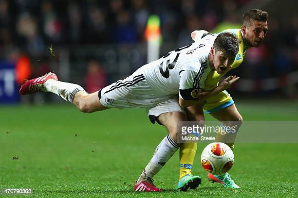 Ben Davies of Swansea City is held back by Dries Mertens of SSC Napoli during the UEFA Europa League Round of 32 First Leg match between Swansea City...