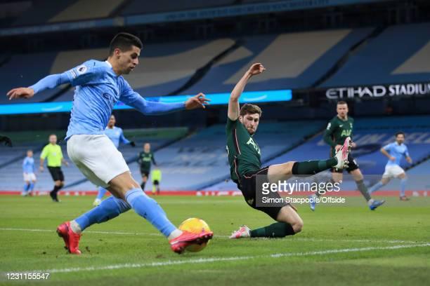 Ben Davies of Tottenham Hotspur attempts to block a cross from Joao Cancelo of Manchester City during the Premier League match between Manchester...