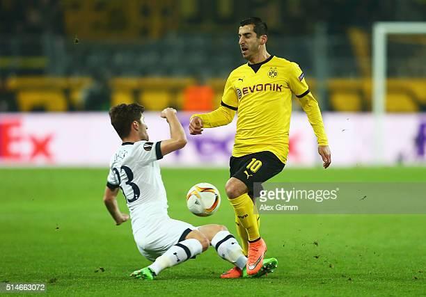 Ben Davies of Tottenham Hotspur tackles Henrikh Mkhitaryan of Borussia Dortmund during the UEFA Europa League Round of 16 first leg match between...