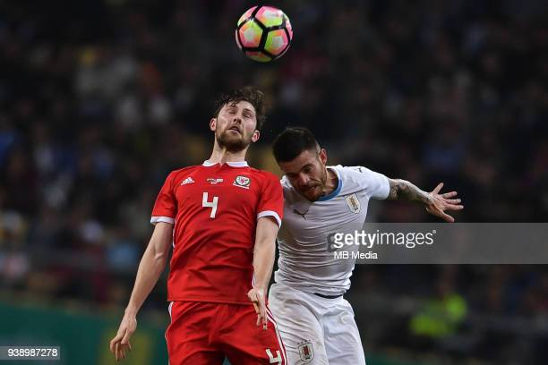 Ben Davies top of Wales national football team heads the ball to make a pass against Nahitan Nandez of Uruguay national football team in their final...