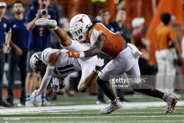 Ben Davis of the Texas Longhorns tackles Jake Bailey of the Rice Owls in the second half at Darrell K Royal-Texas Memorial Stadium on September 18,...