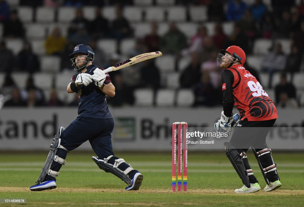 Ben Duckett of Northamptonshire Steelbacks plays a shot as Stuart Poynter of Durham Jets looks on during the Vitality Blast match between Northamptonshire Steelbacks and Durham Jets at The County Ground on August 10, 2018 in Northampton, England.