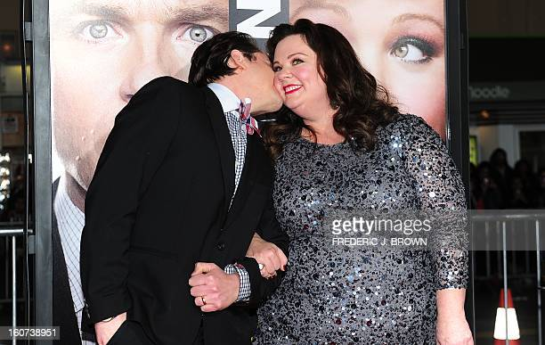 Ben Falcone kisses Melissa McCarthy while posing on arrival for the World Premiere of the film 'Identity Thief' in Los Angeles, California, on...