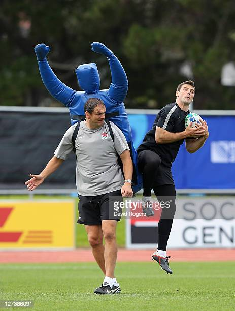 Ben Foden catches the ball as England manager Martin Johnson wears the tackle bag during an England IRB Rugby World Cup 2011 training session at The...