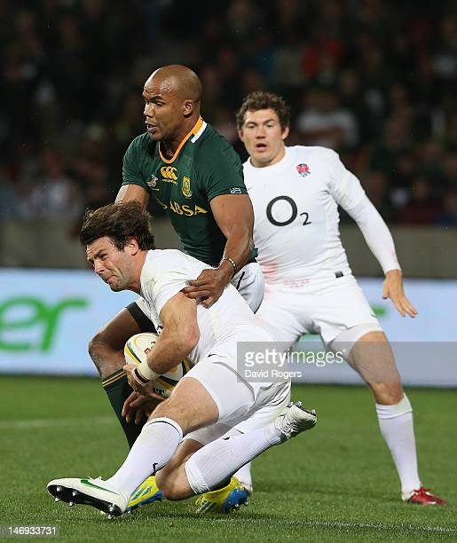 Ben Foden of England is held by JP Pietersen during the third test match between the South Africa Springboks and England at the Nelson Mandela Bay...