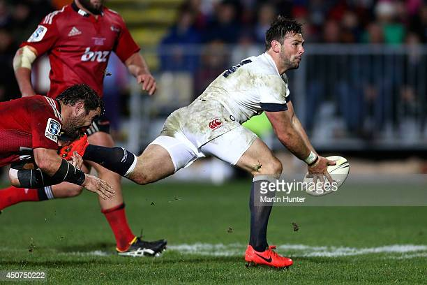 Ben Foden of England looks to pass in the tackle of Corey Flynn of the Crusaders during the International Tour match between the Crusaders and...