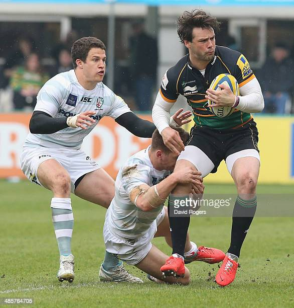 Ben Foden of Northampton is held by Alex Lewington and Fergus Mulchrone during the Aviva Premiership match between Northampton Saints and London...