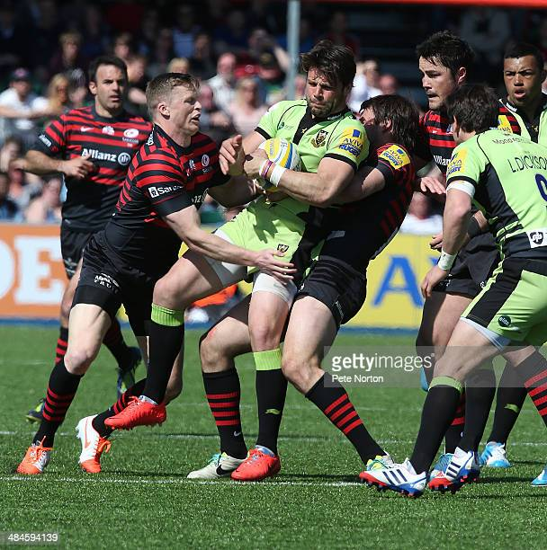 Ben Foden of Northampton Saints is tackled by Chris Ashton and Marcelo Bosch of Saracens during the Aviva Premiership match between Saracens and...