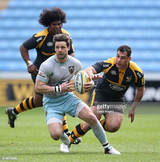 Ben Foden of Northampton turns with the ball watched by George Smith and Ashley Johnson during the Aviva Premiership match between Wasps and...