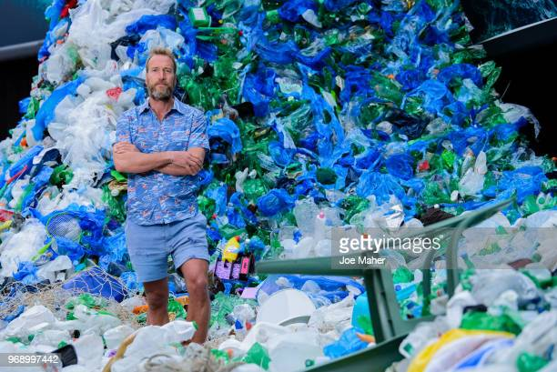 Ben Fogle stands in front giant wave of plastic waste collected from Holywell beach by the Marine Conservation Society is seen on Old Street on June...