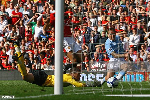 Ben Foster of Manchester United is unable to stop Craig Bellamy of Manchester City scoring his team's third goal during the Barclays Premier League...