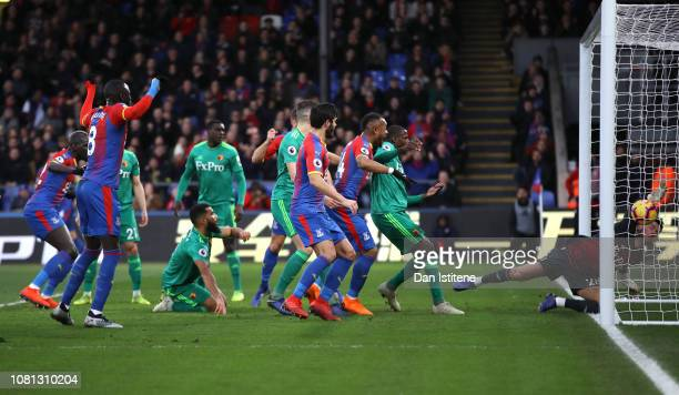Ben Foster of Watford attempts to clear the ball after it rebounds off Craig Cathcart as Crystal Palace score their team's first goal during the...