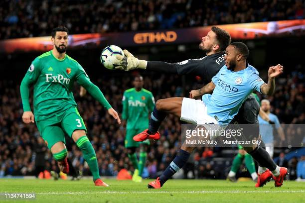 Ben Foster of Watford dives to reach the ball before Raheem Sterling of Manchester City during the Premier League match between Manchester City and...