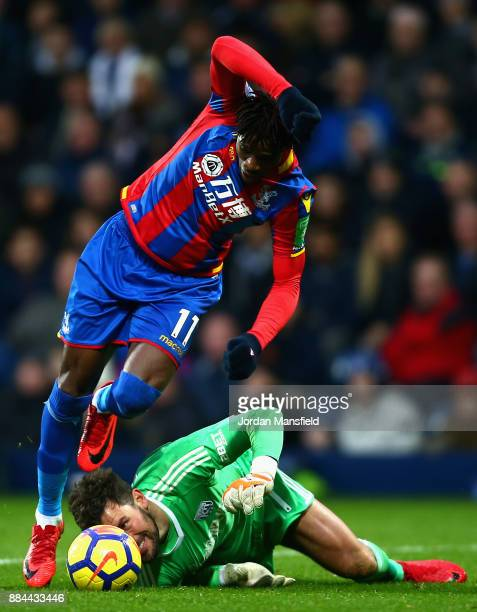 Ben Foster of West Bromwich Albion attempts to head the ball while under pressure from Wilfried Zaha of Crystal Palace during the Premier League...
