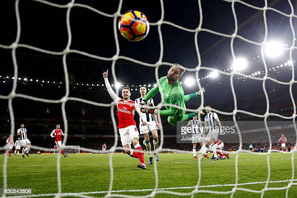 Ben Foster of West Bromwich Albion dives in vain as Olivier Giroud of Arsenal scores the opening goal during the Premier League match between Arsenal...