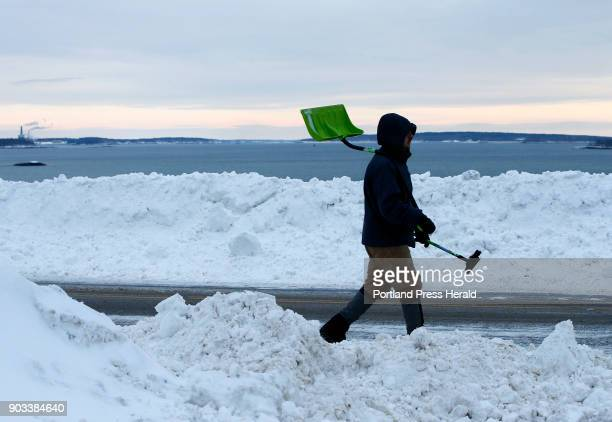 Ben Francis of Portland carries a snow shovel and ice scraper toward his car parked on Cutter Street