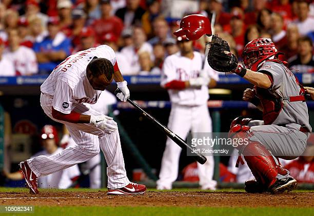 Ben Francisco of the Philadelphia Phillies is hit by a pitch in front of Ryan Harigan of the Cincinnati Reds in Game 2 of the NLDS at Citizens Bank...