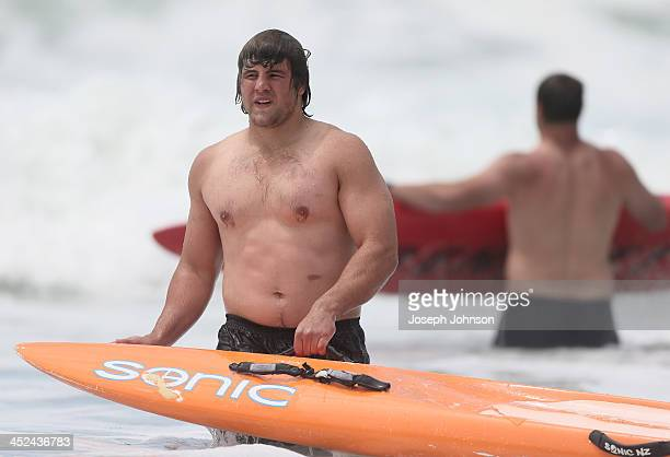 Ben Funnell of the Crusaders in the surf with a board during a surf lifesaving training day on November 29 2013 in Christchurch New Zealand