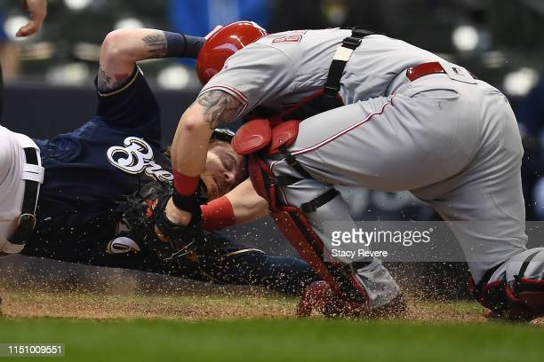 Ben Gamel of the Milwaukee Brewers is tagged out at home plate by Tucker Barnhart of the Cincinnati Reds during the second inning of a game at Miller...