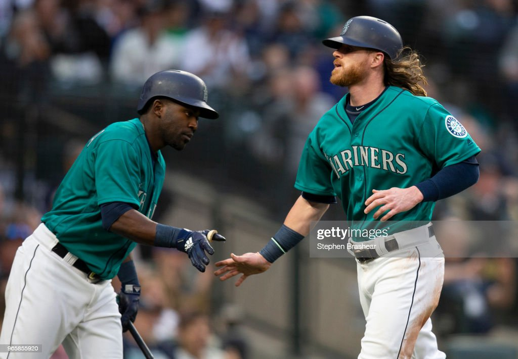 Ben Gamel #16 (R) of the Seattle Mariners is congratulated by Guillermo Heredia #5 of the Seattle Mariners after scoring a run on a hit by Ryon Healy #27 of the Seattle Mariners off of relief pitcher during the fourth inning of a game at Safeco Field on June 1, 2018 in Seattle, Washington.