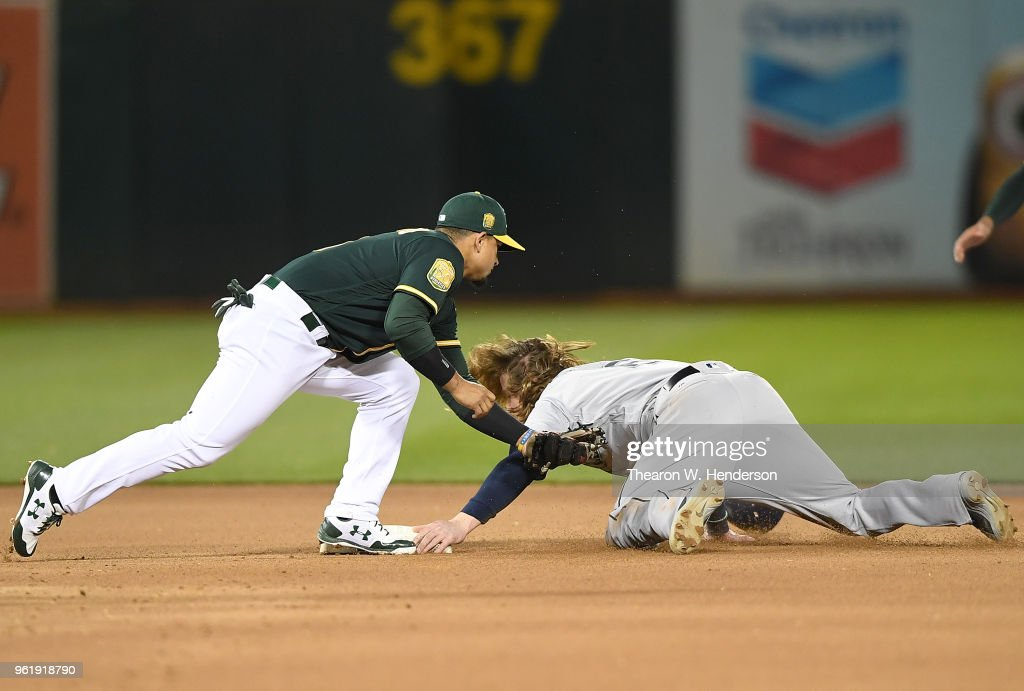Ben Gamel #16 of the Seattle Mariners steals second base beating the throw down to Franklin Barreto #1 of the Oakland Athletics in the top of the seventh inning at the Oakland Alameda Coliseum on May 23, 2018 in Oakland, California.