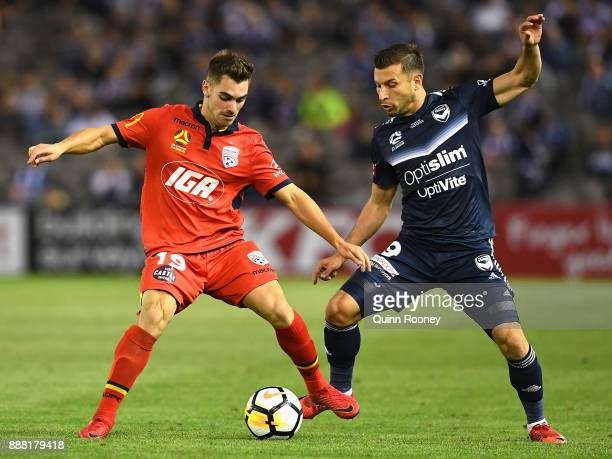 Ben Garuccio of Adelaide United and Kosta Barbarouses of the Victory compete for the ball during the round 10 ALeague match between the Melbourne...