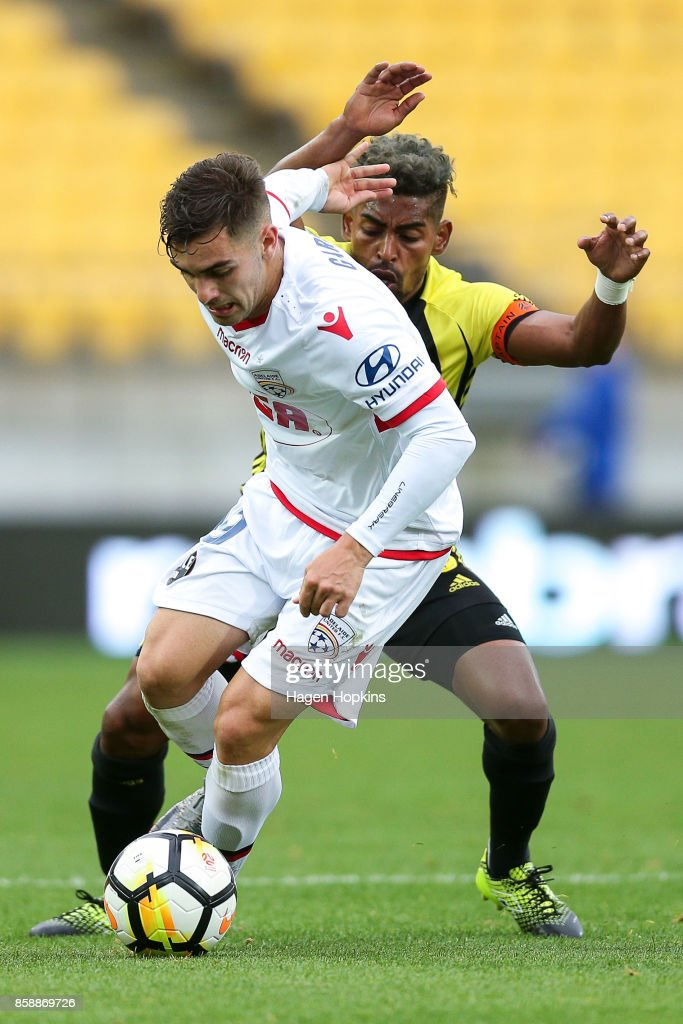 Ben Garuccio of Adelaide United beats the challenge of Roy Krishna of the Phoenix during the round one A-League match between Wellington Phoenix and Adelaide United at Westpac Stadium on October 8, 2017 in Wellington, New Zealand.