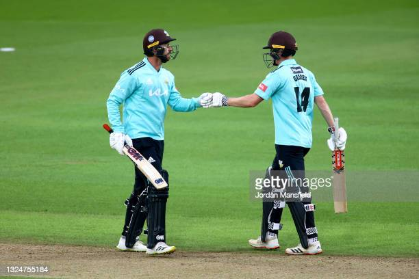 Ben Geddes and Jordan Clark of Surrey punch gloves during the Vitality T20 Blast match between Surrey and Essex Eagles at The Kia Oval on June 21,...
