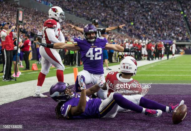 Ben Gedeon and Anthony Harris of the Minnesota Vikings break up a pass to Ricky SealsJones of the Arizona Cardinals in the second quarter of the game...