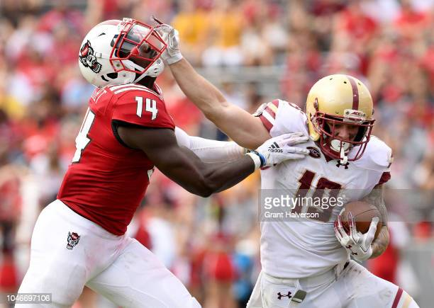Ben Glines of the Boston College Eagles stiff-arms Dexter Wright of the North Carolina State Wolfpack during their game at Carter-Finley Stadium on...
