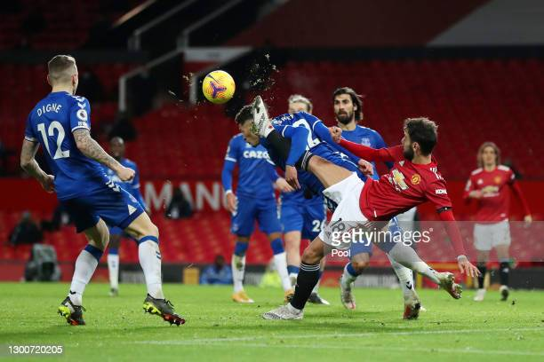 Ben Godfrey of Everton battles for possession with Bruno Fernandes of Manchester United during the Premier League match between Manchester United and...