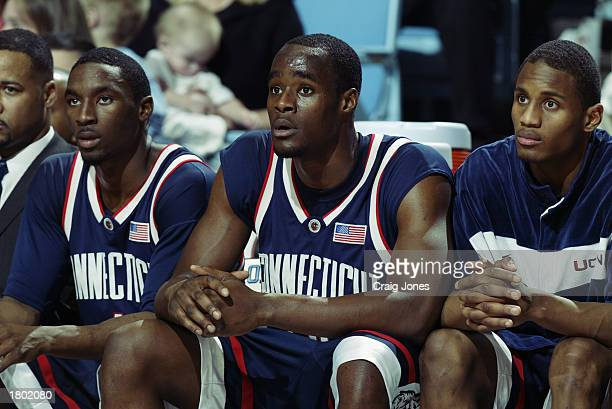 Ben Gordon, Emeka Okafor and Marcus White of the University of Connecticut Huskies watch the action as they rest on the bench during the game against...