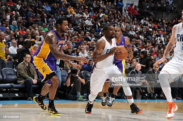 Ben Gordon of the Charlotte Bobcats drives against Earl Clark of the Los Angeles Lakers on February 8 2013 at the Time Warner Cable Arena in...