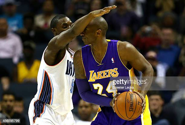 Ben Gordon of the Charlotte Bobcats guards Kobe Bryant of the Los Angeles Lakers during their game at Time Warner Cable Arena on December 14 2013 in...