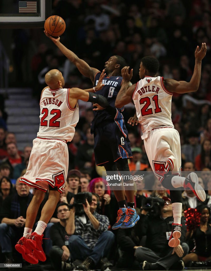 Ben Gordon #8 of the Charlotte Bobcats lays in a shot between Taj Gibson #22 and Jimmy Butler #21 of the Chicago Bulls at the United Center on December 31, 2012 in Chicago, Illinois. The Bobcats defeated the Bulls 91-81.