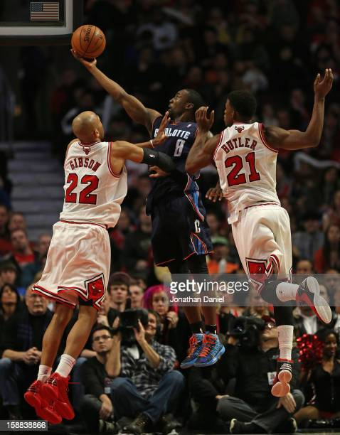Ben Gordon of the Charlotte Bobcats lays in a shot between Taj Gibson and Jimmy Butler of the Chicago Bulls at the United Center on December 31 2012...