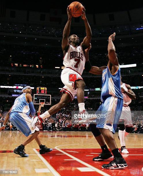 Ben Gordon of the Chicago Bulls drives to the basket between Allen Iverson and Nene of the Denver Nuggets on March 22 2007 at the United Center in...