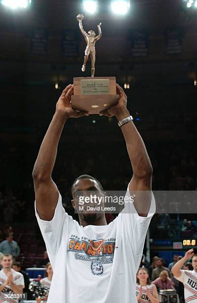 Ben Gordon of the Connecticut Huskies holds the tournament MVP trophy following his team's 6158 victory over the Pittsburgh Panthers during the Big...