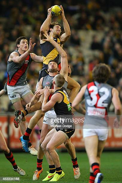 Ben Griffiths of the Tigers takes a high mark over Cale Hooker of the Bombers during the round 20 AFL match between the Richmond Tigers and the...