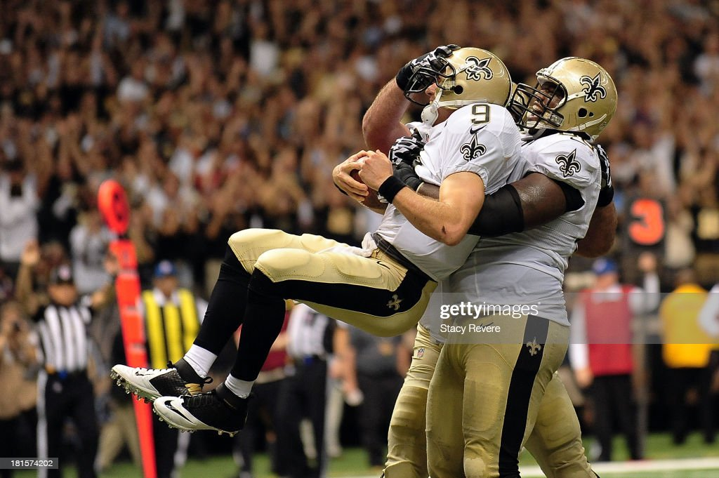 Ben Grubbs #66 of the New Orleans Saints celebrates a touchdown with Drew Brees #9 during a game against the Arizona Cardinals at the Mercedes-Benz Superdome on September 22, 2013 in New Orleans, Louisiana. The Saints defeated the Cardinals 31-7.