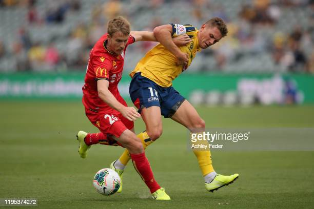 Ben Halloran of Adelaide United is contested by Gianni Stensess of the Central Coast Mariners during the round 11 ALeague match between the Central...