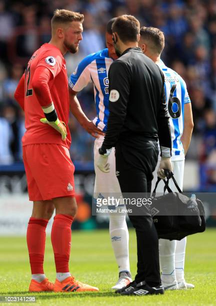 Ben Hamer of Huddersfield Town speaks to medical staff after a challenge by Nathaniel MendezLaing of Cardiff City during the Premier League match...