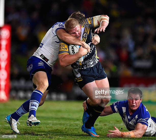 Ben Hannant of the Cowboys is tackled by Trent Hodkinson and Joshua Jackson of the Bulldogs during the round nine NRL match between the North...