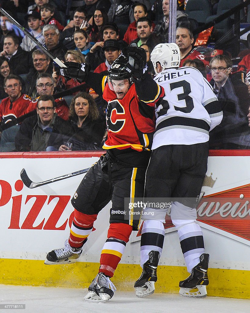 Ben Hanowski #58 of the Calgary Flames collides with Willie Mitchell #33 of the Los Angeles Kings during an NHL game at Scotiabank Saddledome on March 10, 2014 in Calgary, Alberta, Canada. The Kings defeated the Flames 3-2.